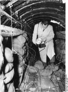 """Zentralbild 24.4.1956 USA-Spionage Tunnel unter DDR-Gebiet Der amtierende Militärkommandant des sowjetischen Sektors von Berlin, Oberst Kozjuba, gab am Montagabend (23.4.56) auf einer Pressekonferenz vor zahlreichen in- und ausländischen Journalisten bekannt, dass am 22.4.1956 von sowjetischen Truppen eine amerikanische Abhörzentrale im demokratischen Sektor Berlins ausgehoben wurde. Amerikanische Stellen hatten im Gebiet von Altglienicke einen etwa 300 m langen Stollen angelegt, der zu den Fernmeldelinien der sowjetischen Truppen sowie zu den Fernmeldelinien der Deutschen Demokratischen Republik lief. Durch den Stollen ziehen sich Kabelleitungen, die vom amerikanischen Sektor ausgehen und an die Kabelleitungen der sowjetischen Truppen angeschlossen wurden. Im Anschluß an die Pressekonferenz fand eine Besichtigung der amerikanischen Abhörzentrale statt. UBz.: Der """"Stern""""-Bildreporter überschreitet die Stacheldrahtsperre, dies sich kurz vor der von den Amerikanern errichteten Barriere befindet.."""